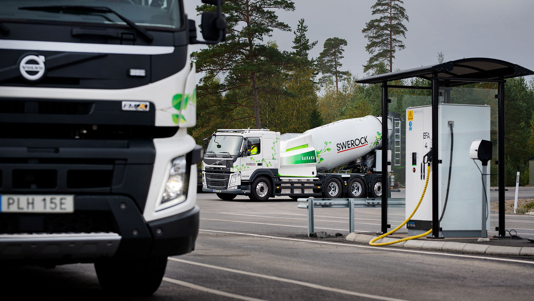 The Volvo FMX and FM parked near a charging station