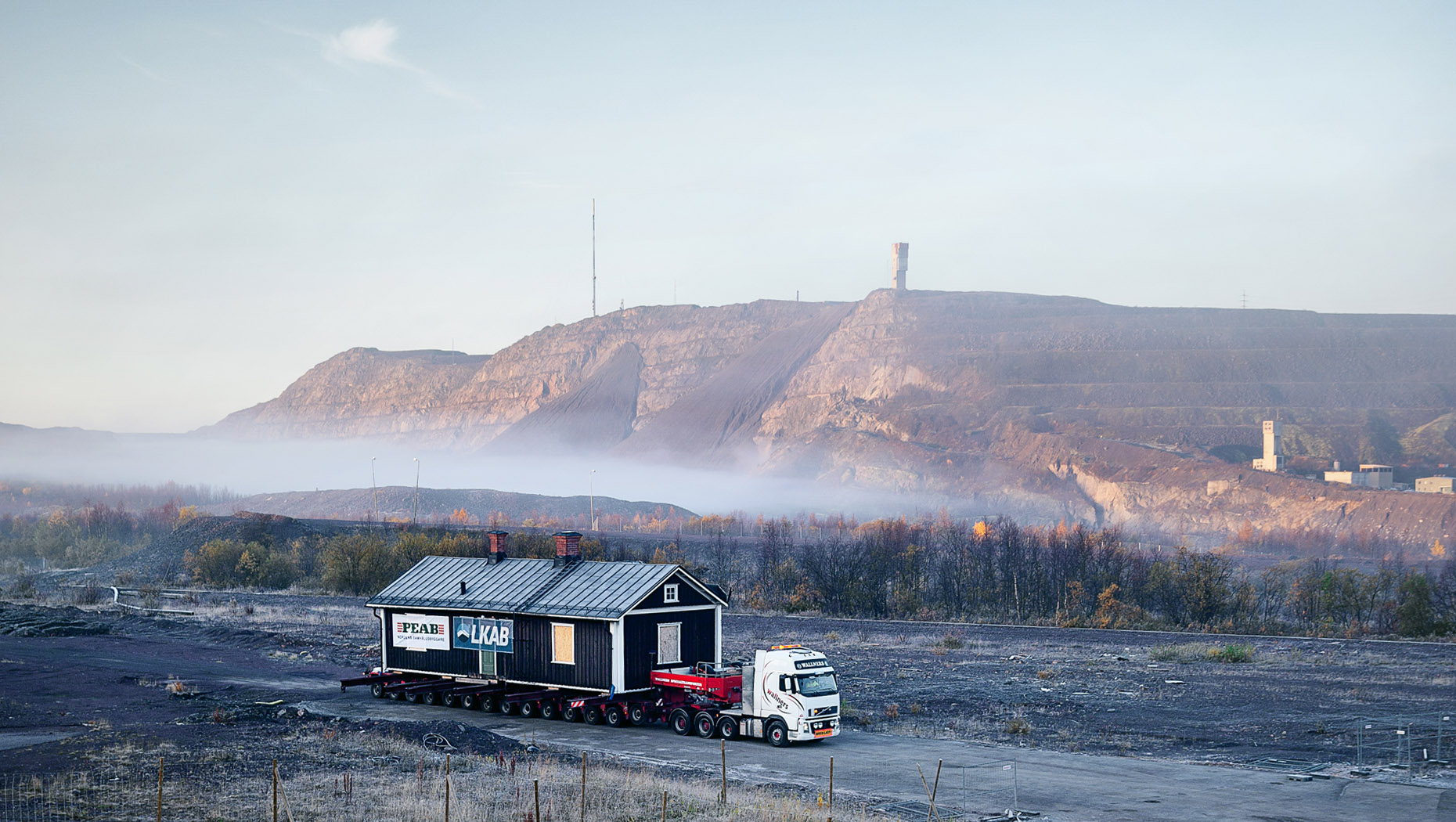 A Volvo FH truck transports a building in Kiruna, northern Sweden, surrounded by mist