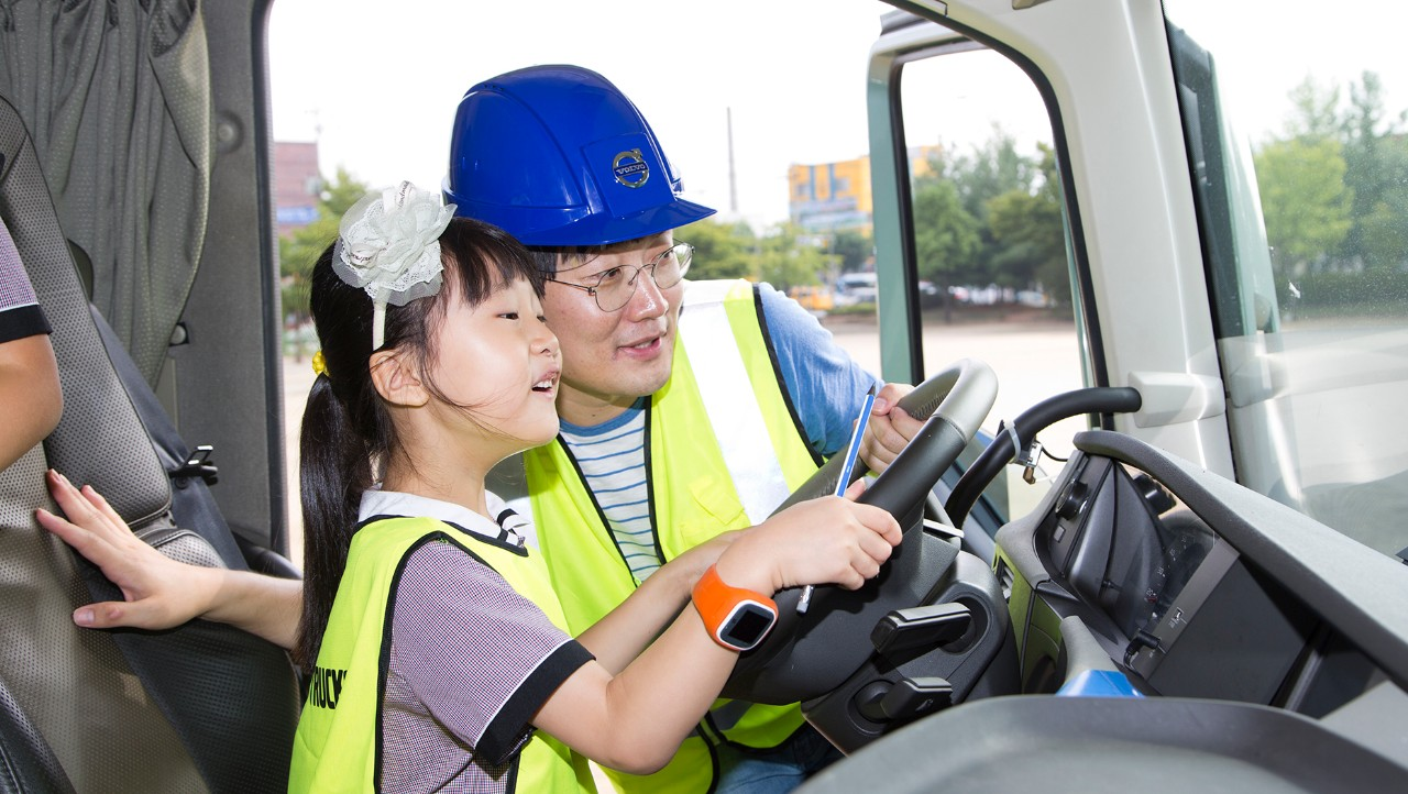 A man and child sitting in the driver seat of a truck