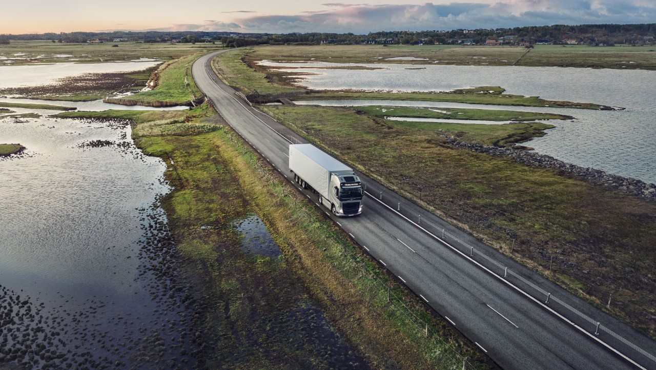 A Volvo FH with I-Save drives across a bridge over a lake