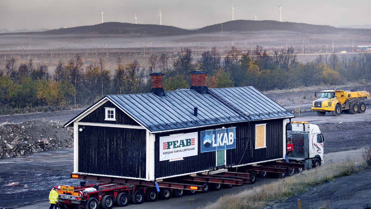 Side view of the Kiruna museum being transported with windmills in the background