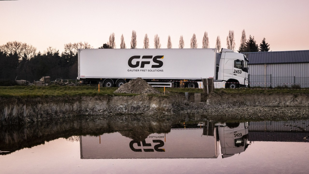 The Volvo FH with I-Save passes a lake and is reflected in the water