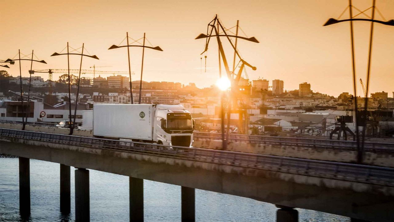 The Volvo FH with I-Save crosses a bridge at sunset with a Spanish town in the background