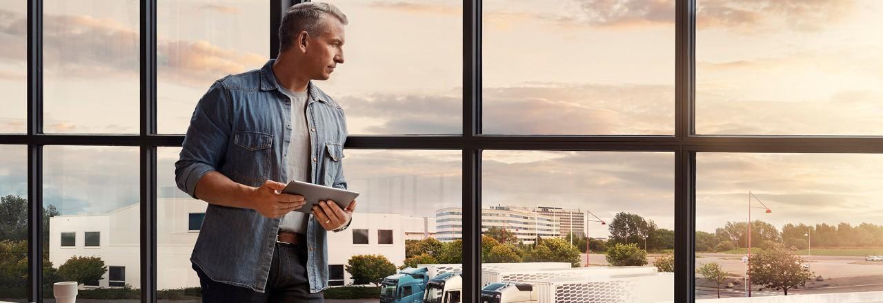 Мужчина с планшетом стоит у окна и смотрит на свой парк грузовых автомобилей