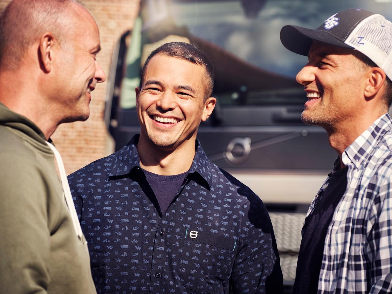 Трое улыбающихся людей крупным планом перед грузовым автомобилем Volvo