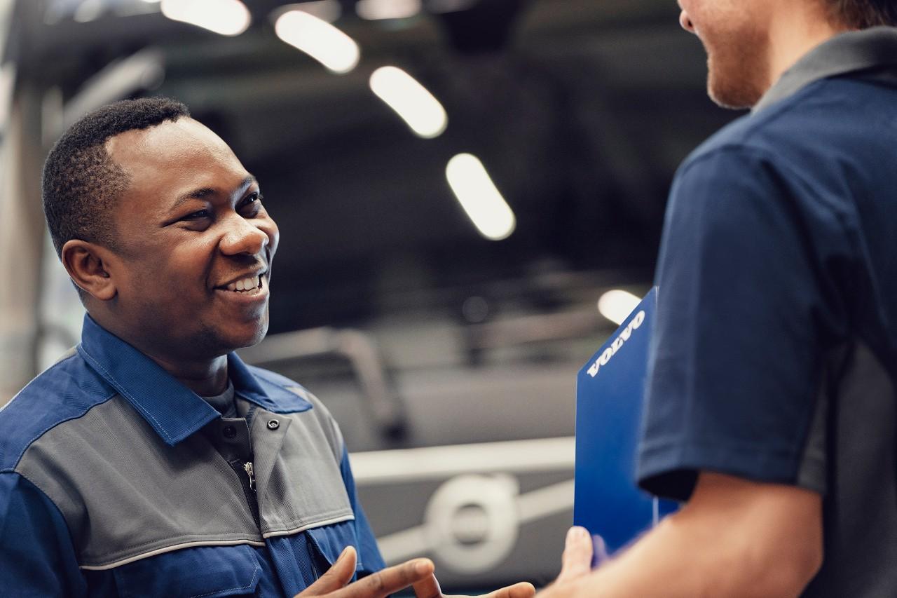 Улыбающийся специалист сервисной службы Volvo разговаривает с коллегой