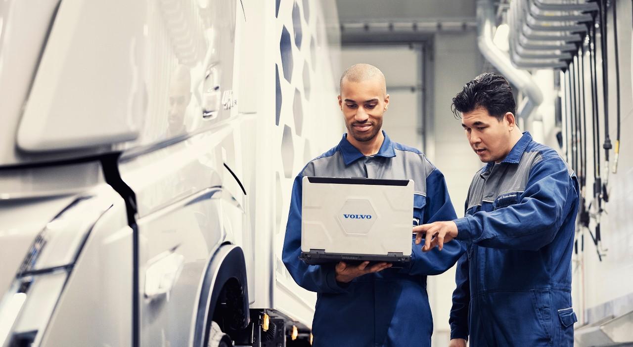 Два специалиста по обслуживанию Volvo смотрят на экран ноутбука, стоя рядом с грузовиком
