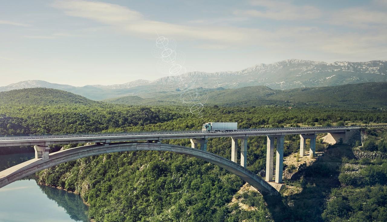 รถบรรทุกวอลโว่ที่เชื่อมต่อกับระบบขณะเคลื่อนผ่านสะพานในสถานที่ห่างไกล